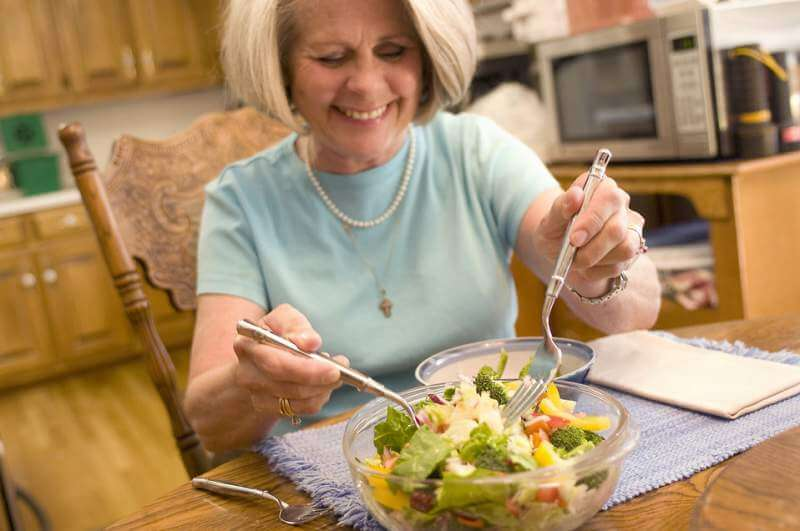woman eating a fresh salad - 5 Useful Hygiene Tips for a Healthier Bedtime Routine