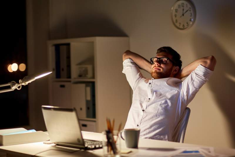 man-with-laptop-stretching-at-night-office