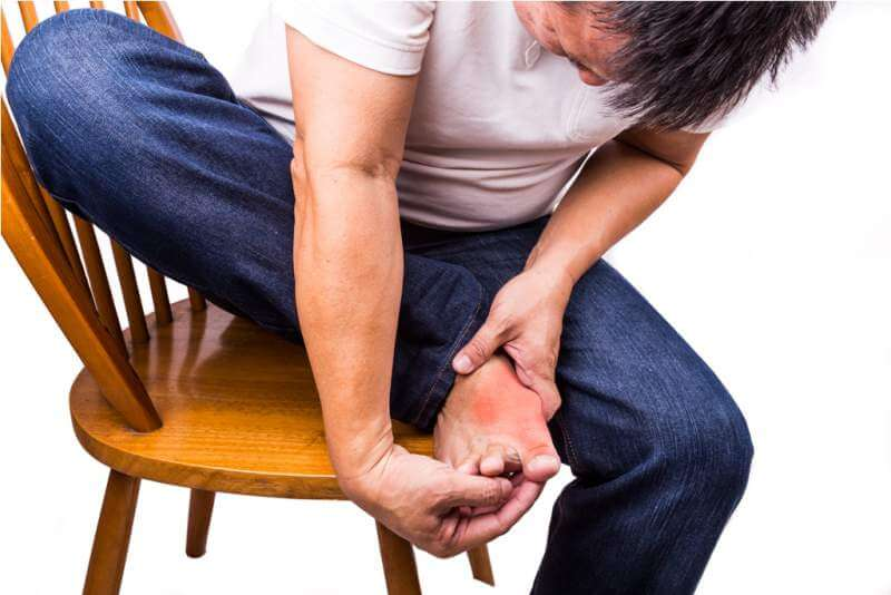 man-embraces-foot-with-painful-and-swollen-gout