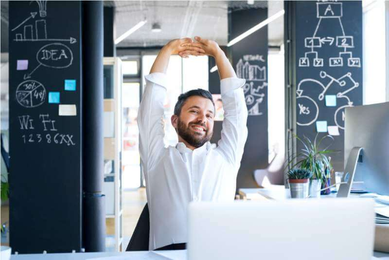 businessman-at-the-desk-in-his-office-stretching