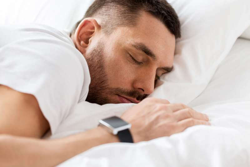 close-up-of-man-with-smartwatch-sleeping-in-bed