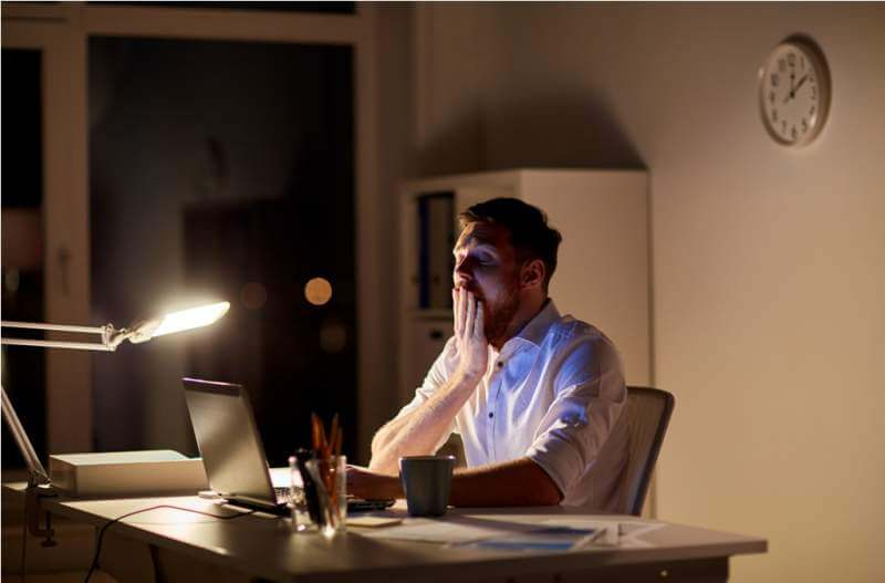 man-with-laptop-and-coffee-working-at-night