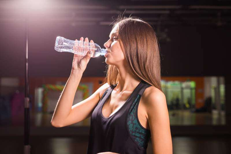 fitness-woman-drinking-water-from-bottle-muscular