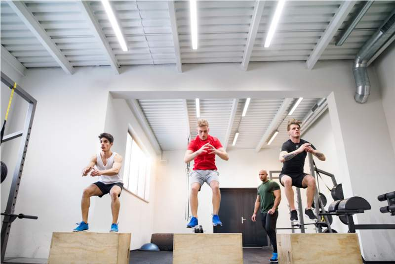 men-in-gym-with-trainer-exercising-on-fit-boxes