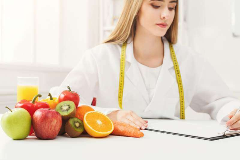 nutritionist-desk-with-fruit-and-measuring-tape