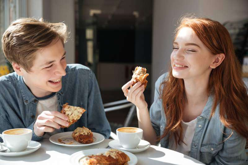pretty-couple-eating-in-cafe