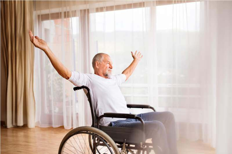 senior-man-sitting-on-wheelchair-at-home