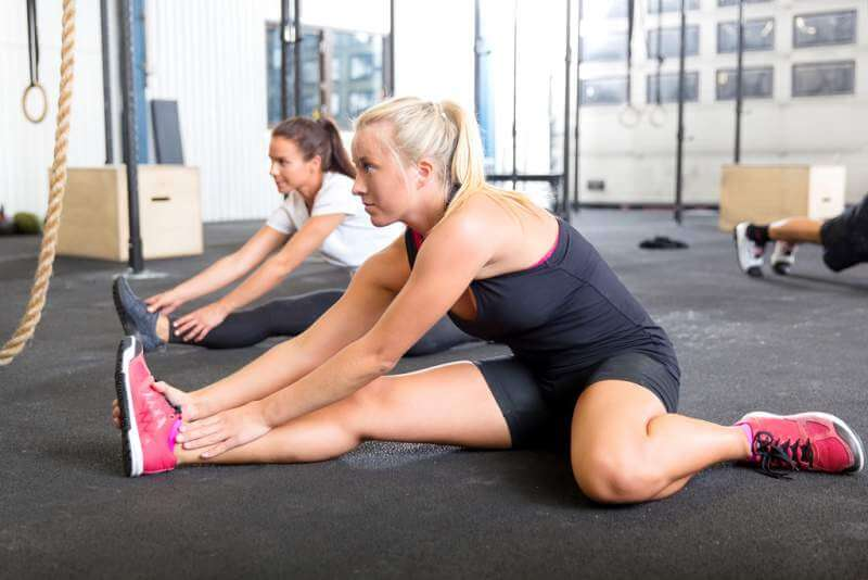 two-women-stretching-at-the-fitness-gym
