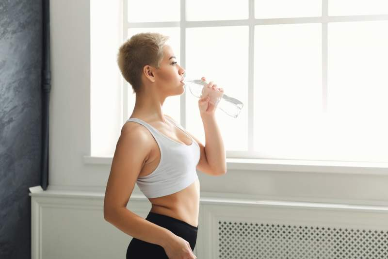 fitness-woman-drinking-water-at-gym-on-white