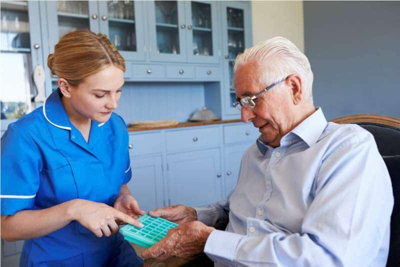 nurse-helping-senior-man-to-organize-medication