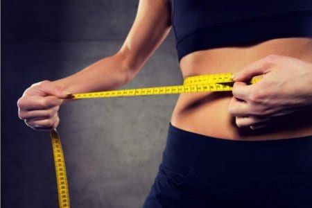 woman-measuring-waist-by-tape-in-gym