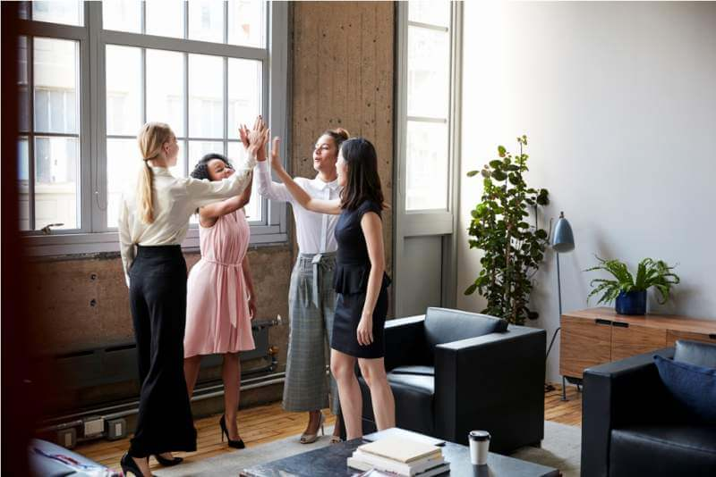 female-colleagues-high-five-at-a-motivational