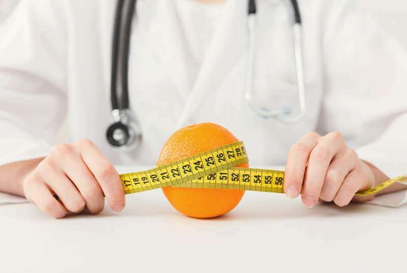 nutritionist-doctor-with-fruit-and-measuring-tape