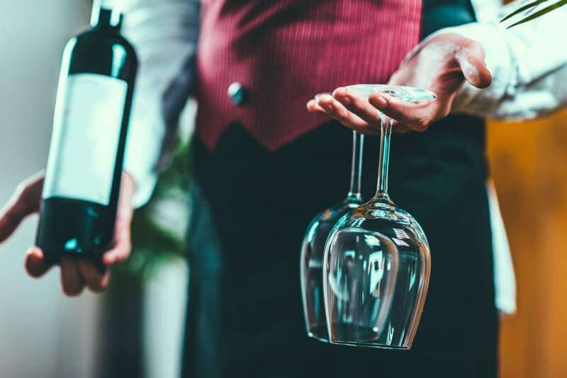 sommelier-holding-wine-bottle-and-wine-glasses