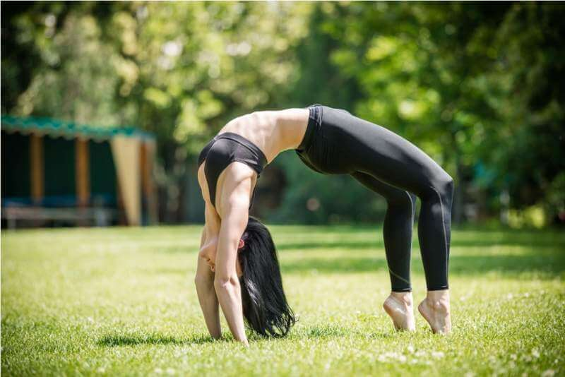 young-woman-performing-bridge-exercise-in-park