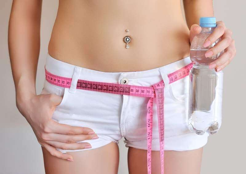 close-up-of-female-belly-with-measuring-tape