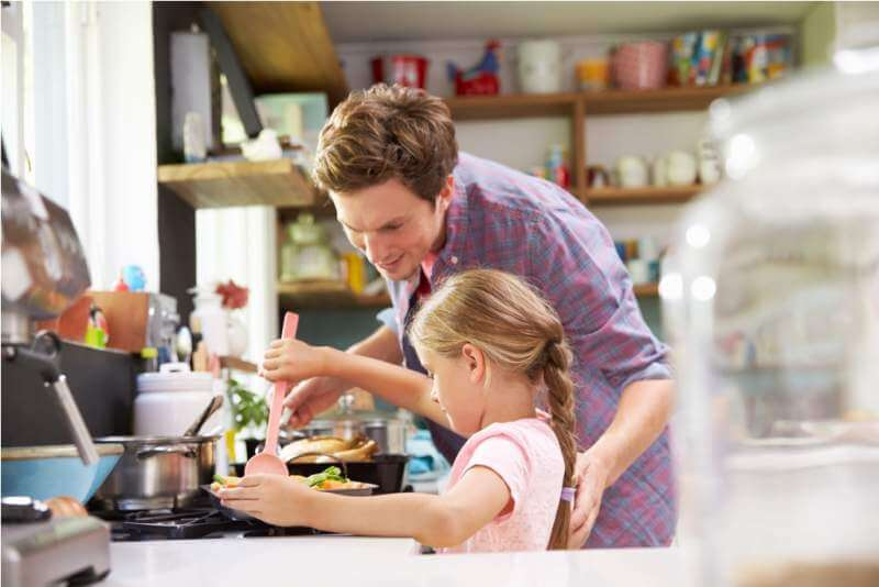 daughter-helping-father-to-cook-meal-in-kitchen
