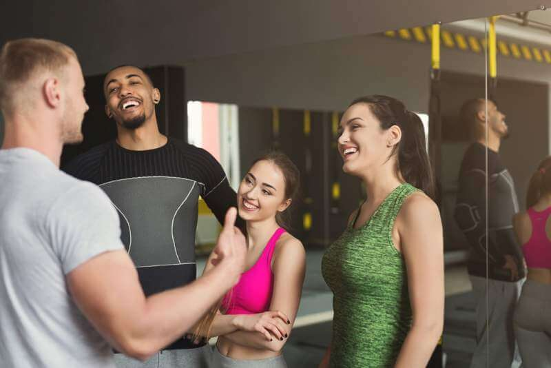 group-of-sporty-people-talking-at-gym
