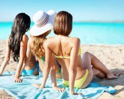group-of-women-in-swimwear-sunbathing-on-beach