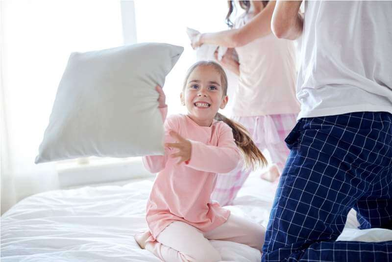 happy-family-having-pillow-fight-in-bed-at-home