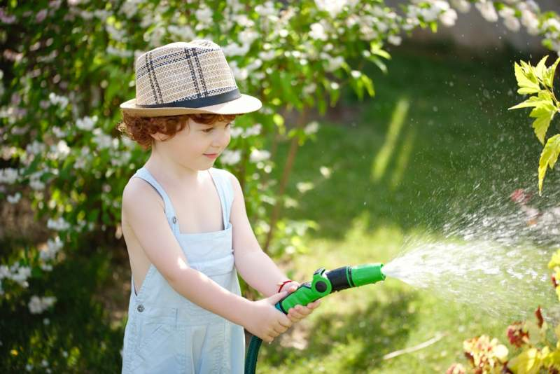 little-boy-watering-the-garden-with-hose