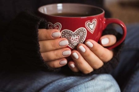woman-with-beautiful-manicure-holding-a-red-cup