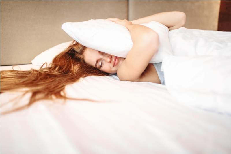 beautiful-woman-hugs-pillow-waking-up