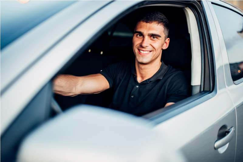 happy-male-driver-in-car-advertising