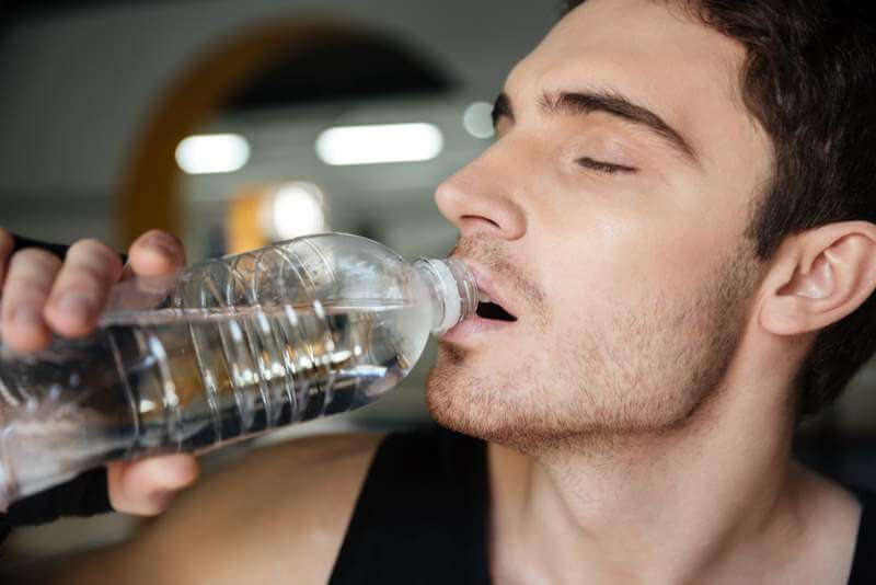 man-sportsman-drinking-water-after-training