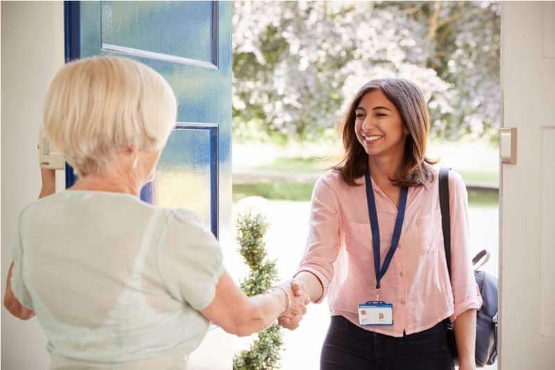 senior-woman-greeting-female-care-worker