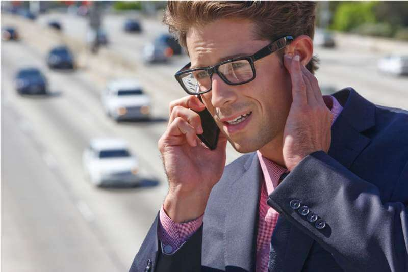 businessman-speaking-on-mobile-phone-by-noisy