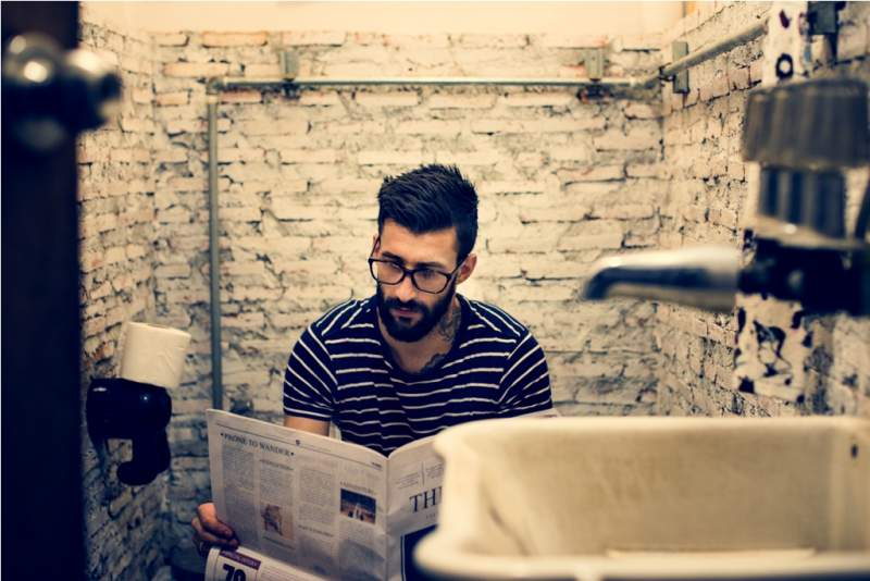 man-in-a-restroom-reading-newspaper