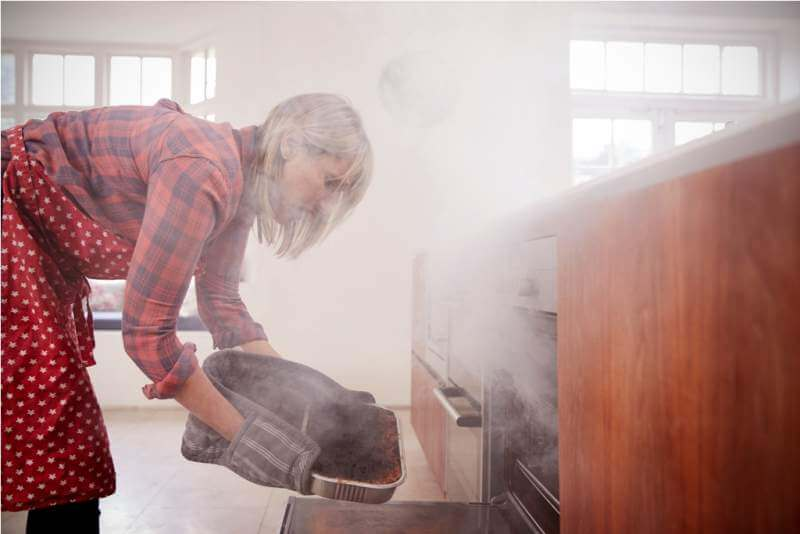 middle-aged-woman-opening-smoke-filled-oven