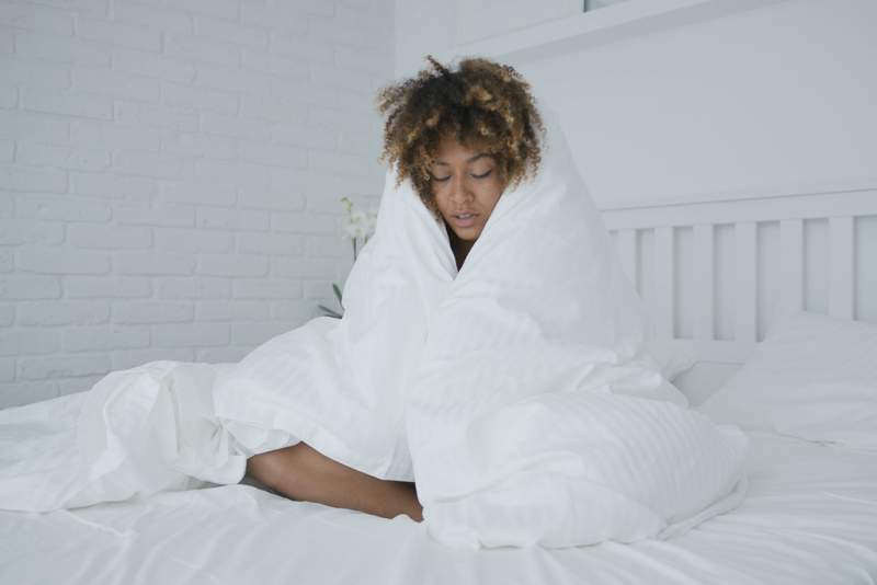 sleepy-woman-cuddling-in-blanket