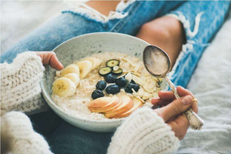 woman-in-jeans-and-sweater-eating-healthy-oatmeal