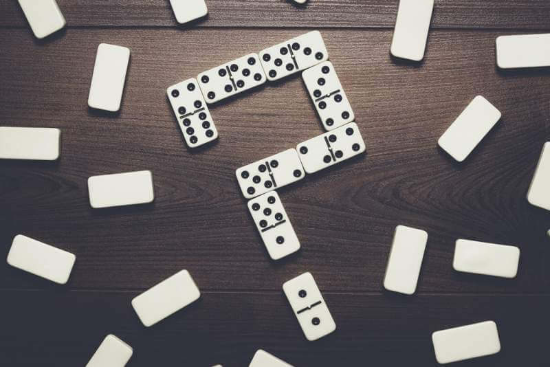 domino-pieces-forming-question-mark-on-wooden