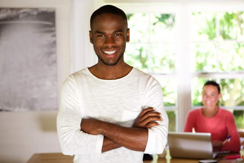 happy-young-african-man-standing-with-his-arms