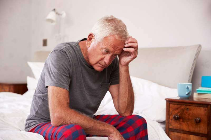 senior-man-sitting-on-bed-at-home-suffering
