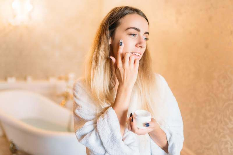 smiling-woman-in-white-bathrobe-facial-skincare