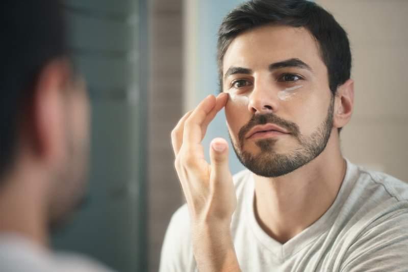 young-man-applying-anti-aging-lotion-fot-skin