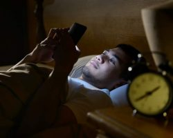 young-man-using-a-smartphone-in-his-bed-at-nightjpg