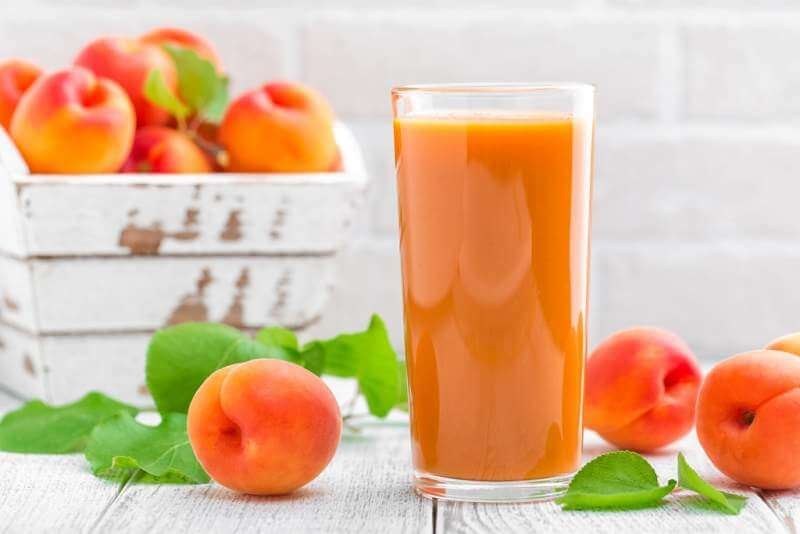 apricot-juice-and-fresh-fruits-with-leaves