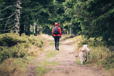 happy-woman-hiking-walking-with-dog