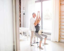 senior-male-physiotherapist-working-with-a-female