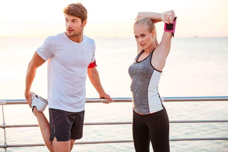 athletic-couple-stretching-out-after-running