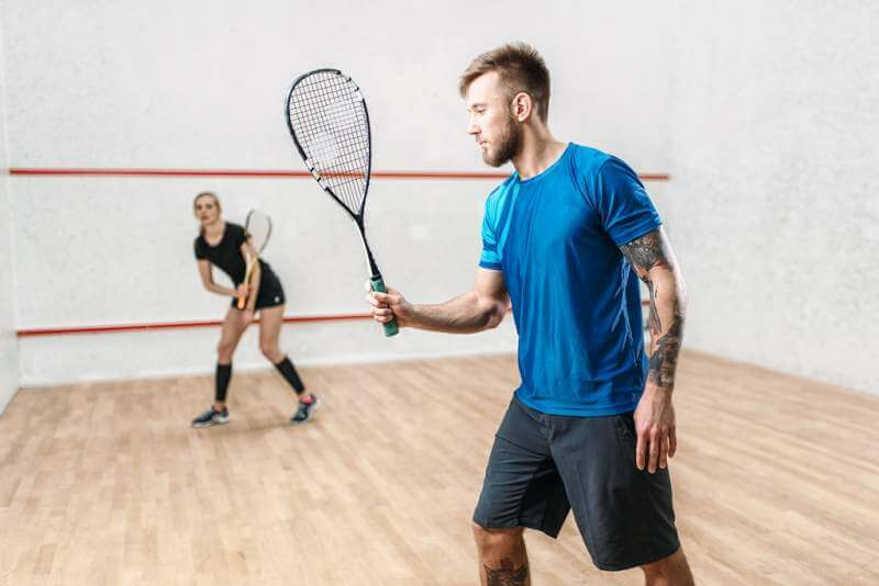 active-couple-with-rackets-play-squash-game