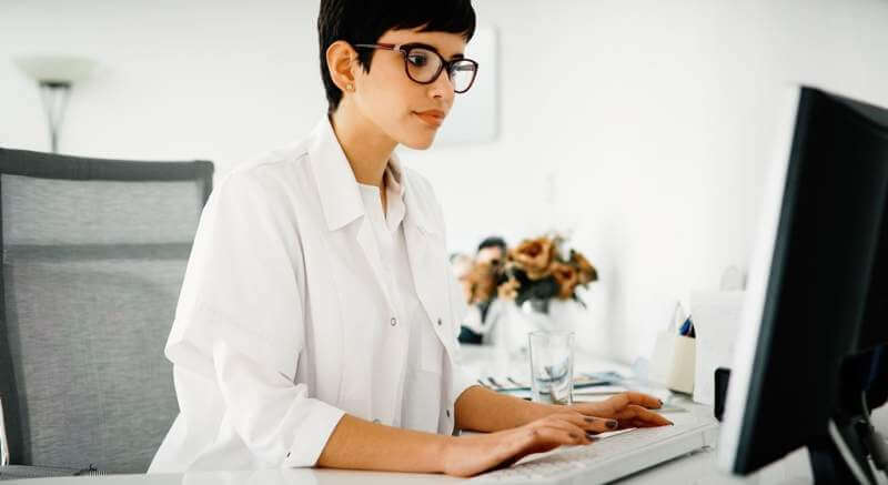 beautiful-female-doctor-typing-receipt