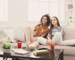 smiling-female-friends-watching-tv-at-home
