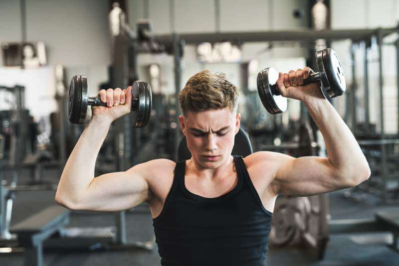 young-fit-man-in-gym-exercising-with-dumbbells