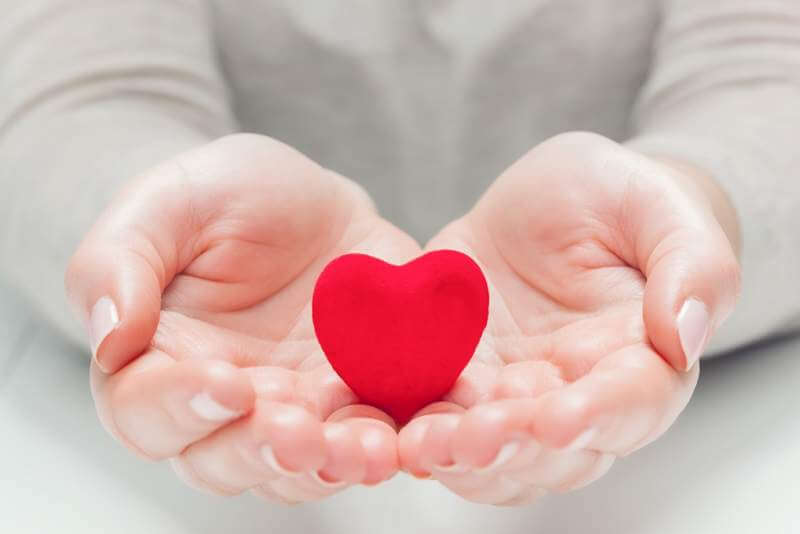 small-red-heart-in-womans-hands-in-a-gesture